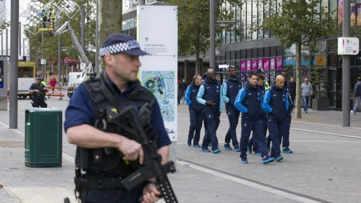Players and staff of the France football team go for a walkabout around Wembley Stadium escorted by British armed police