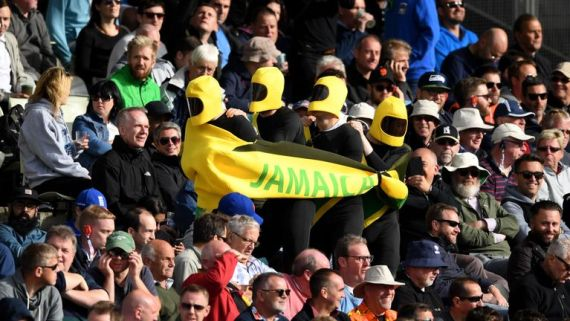 Fans dressed as the Jamaican bobsled team glide into their seats