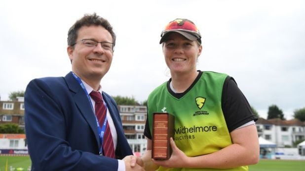 Wisden editor Lawrence Booth hands Anya Shrubsole her leather-bound copy