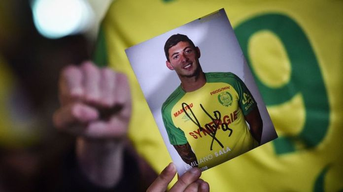 A member of the public holds up a photograph of Sala during a vigil in Nantes