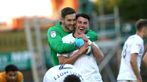 Newport County goalkeeper Joe Day (left) and Regan Poole celebrate their penalty shoot-out success against Mansfield