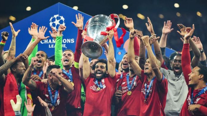 Mohamed Salah holds the Champions League trophy in the air