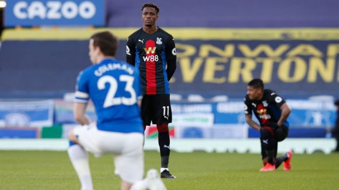 Wilfried Zaha opts against taking a knee ahead of Crystal Palace's Premier League clash with Everton. (Darren Staples/Sportimage via AP Images)