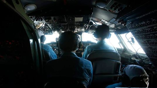 Military officers work within the cockpit of an aircraft belonging to the Vietnamese airforce during a search and rescue mission off Vietnam's Tho Chu island