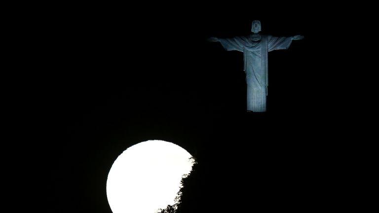 A full moon illuminates the Christ statue in Rio de Janeiro, Brazil
