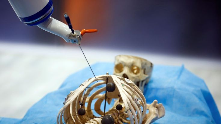 A Siasun Robot and Automation Corporation robot simulates the use of a medical instrument on a model of a human skeleton at the World Robot Conference in Beijing