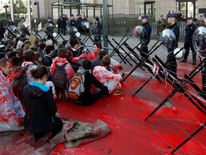 Demonstrators with red paint sit in front of the European Council building during a protest against CETA