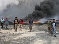 Tribal fighters walk near burning oil wells in Qayyara