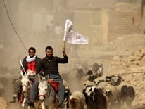 A man fleeing Bazwaia village carries a white flag as he arrives at a checkpoint