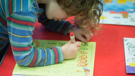 A young girl writes letters at a playgroup for pre-school aged children in Chilcompton near Radstock in Somerset, England