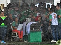 Relatives mourn over a coffin of one of the team's players