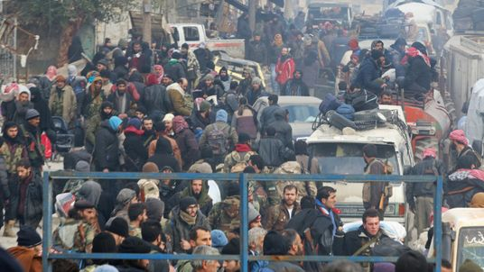 Rebel fighters and civilians gather as they wait to be evacuated from eastern Aleppo