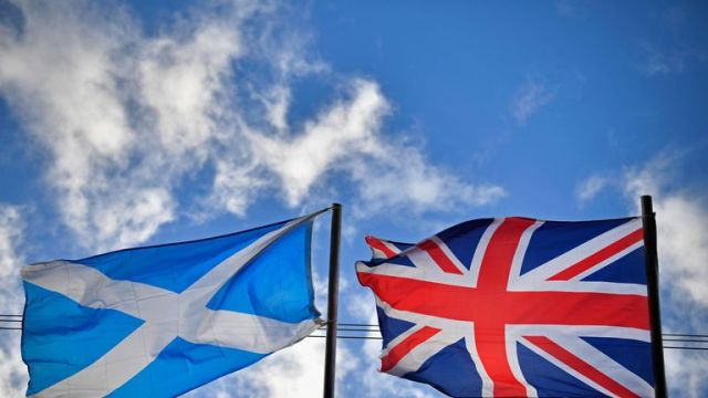 A saltire flag and Union Jack flutter in the wind