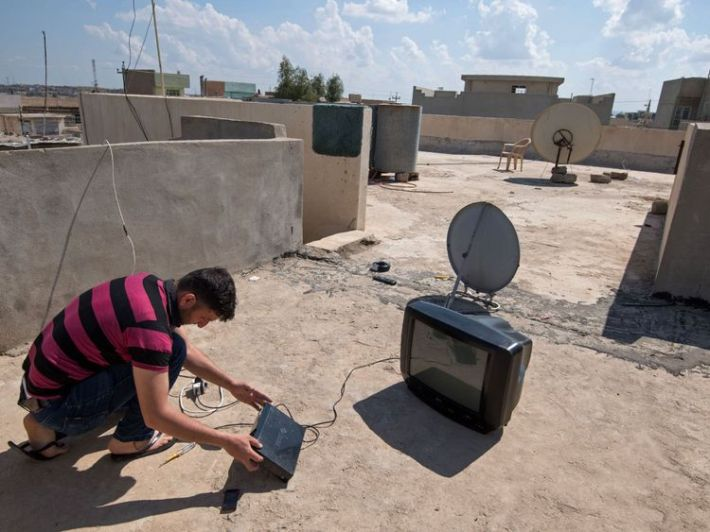 A man installs a satellite dish on the rooftop of a house in eastern Mosul