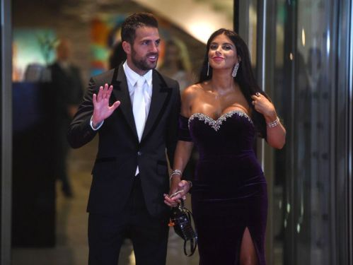 Chelsea's football player Cesc Fabregas and his wife pose on a red carpet upon arrival to attend Argentine football star Lionel Messi and Antonella Roccuzzo's wedding