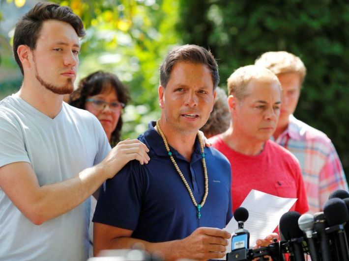 Don Damond is comforted by his son Zach Damond as he speaks to the media about his fiance, Justine Damond who was fatally shot by Minneapolis police in Minneapolis