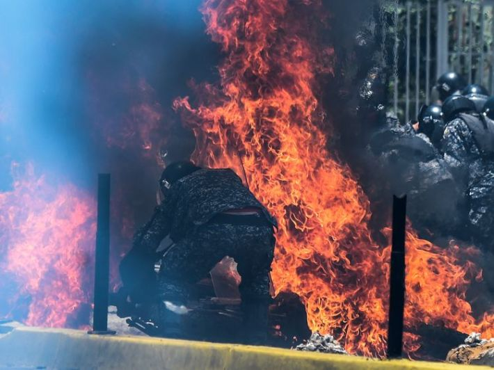 Police motorbikes burn after a device exploded as they drove past