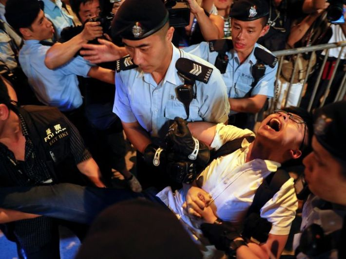 Joshua Wong shouts as he is carried by policemen during a protest