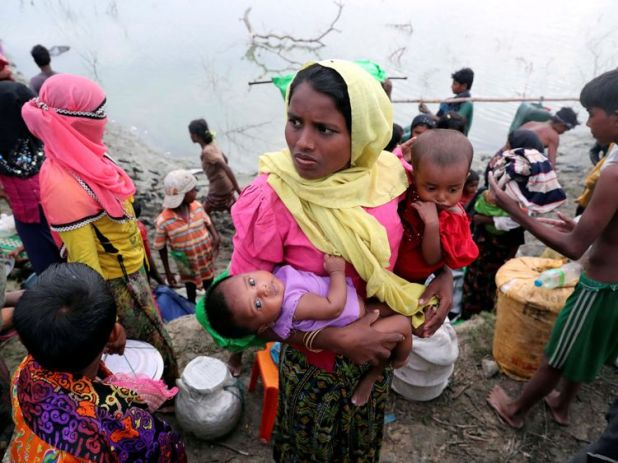 A Rohingya refugee women from Buthidaung carries her children after crossing the Naf River with an improvised raft to reach Bangladesh