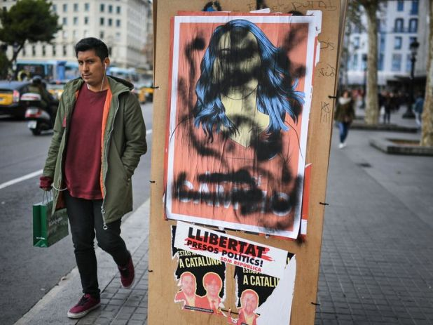 A man walks past a defaced election poster