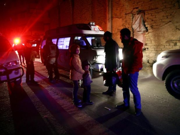People stand near an ambulance during medical evacuation from the besieged town of Douma, eastern Ghouta to Damascus