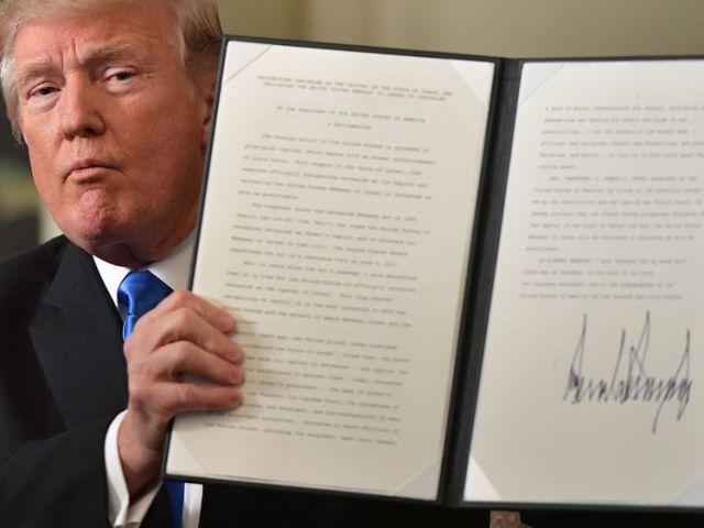 President Trump holds up a signed memorandum after he delivered his statement on Jerusalem