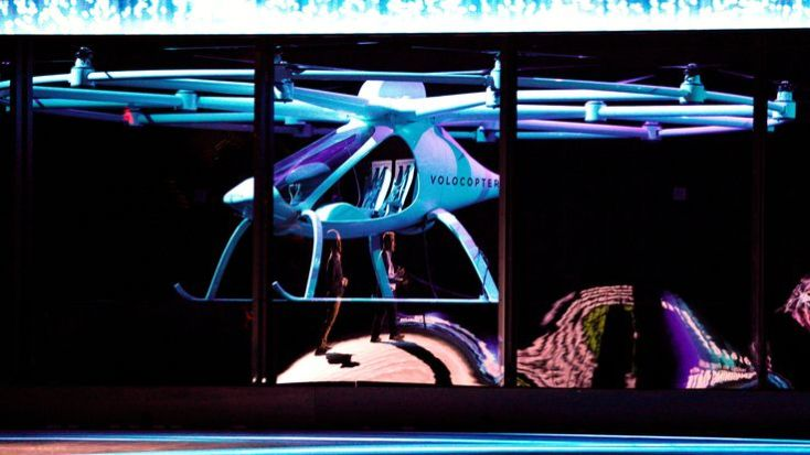 Brian Krzanich, Intel CEO, (R) is reflected in protective glass as atwo-seater Volocopter drone flies on stage at the Intel Keynote address at CES