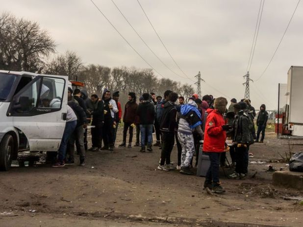 Migrants line up during a food distribution from aid associations in Calais in January