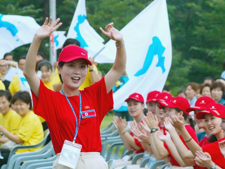 North Koreans (red shirts) cheer as South Koreans (yellow shirts) wave unified Korean peninsula flags in 2003
