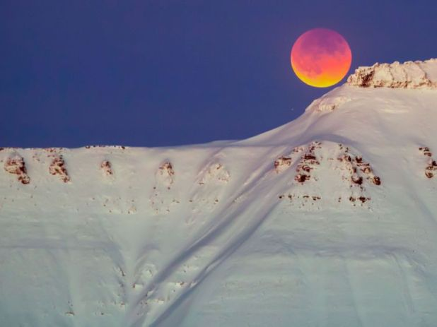 The moon rises over Svalbard in Norway