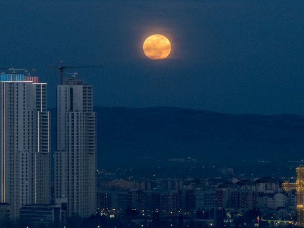 The moon rises next to the highest buildings in Skopje, Macedonia