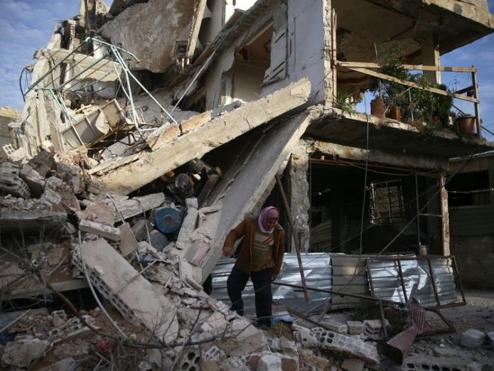 A person inspects damaged building in the besieged town of Douma UN calls for end to 'hell on earth' violence in eastern Ghouta UN calls for end to 'hell on earth' violence in eastern Ghouta skynews syria douma world 4236558