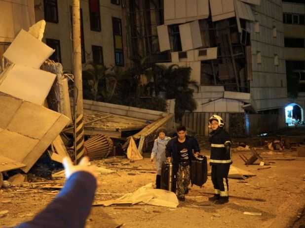 Two guests are escorted by rescue workers from the damaged Marshal Hotel in Hualien, eastern Taiwan early February 7, 2018, after a strong earthquake struck the island. A hotel on the east coast of Taiwan has collapsed after a 6.4-magnitude earthquake, the government said. / AFP PHOTO / YANG JEN-FU / Taiwan OUT (Photo credit should read YANG JEN-FU/AFP/Getty Images)