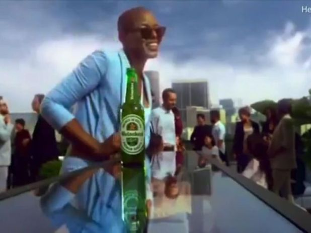 The bottle passes several black people before reaching the woman. Pic: Heineken
