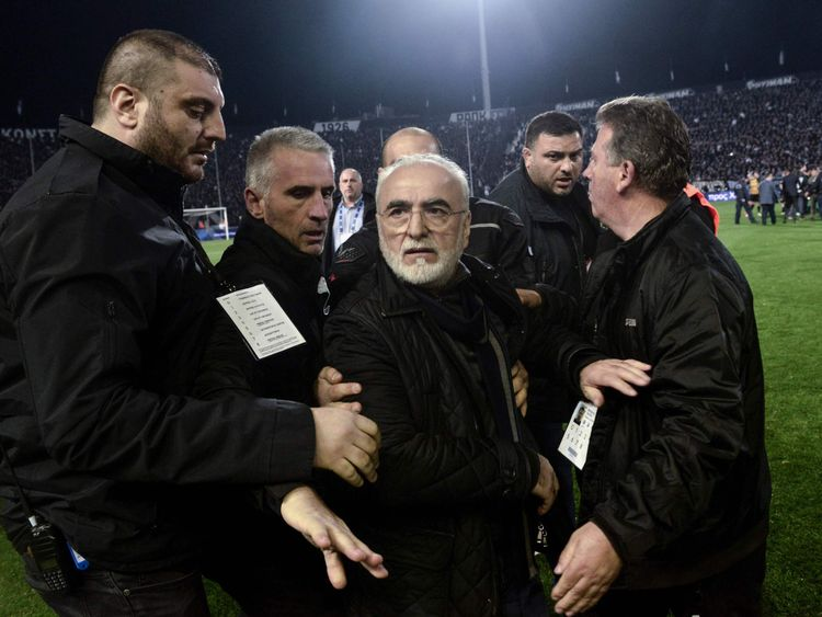Paok president Ivan Savvidis, centre, is escorted off the pitch