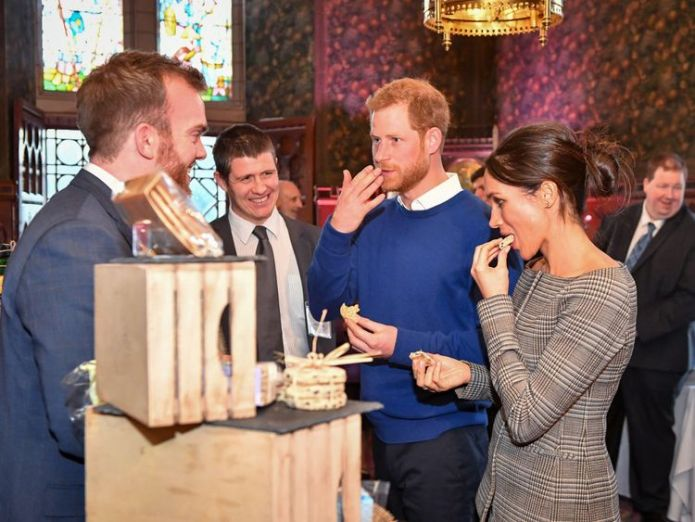Prince Harry and Meghan Markle taste traditional Welsh cakes during a visit to Cardiff Castle