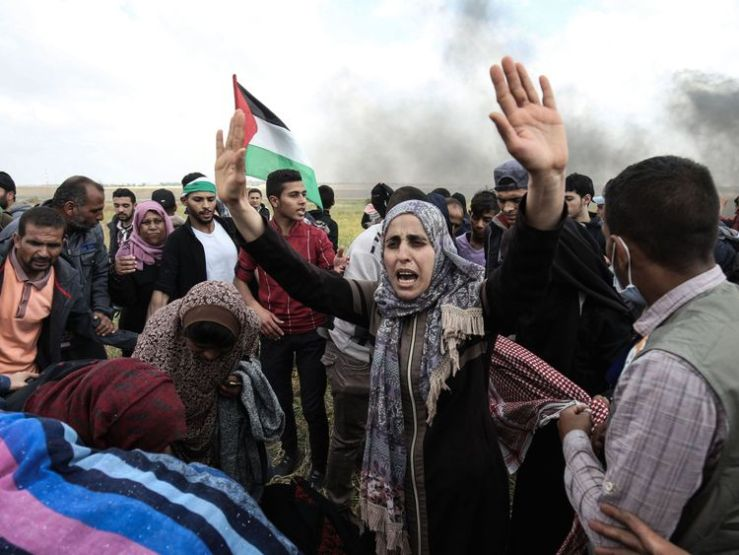 Palestinian protesters wave their national flag and gesture during a demonstration commemorating Land Day near the border with Israel, east of Khan Yunis, in the southern Gaza Strip on March 30, 2018
