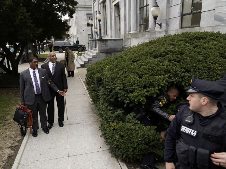 Bill Cosby watches as a protester struggles with police