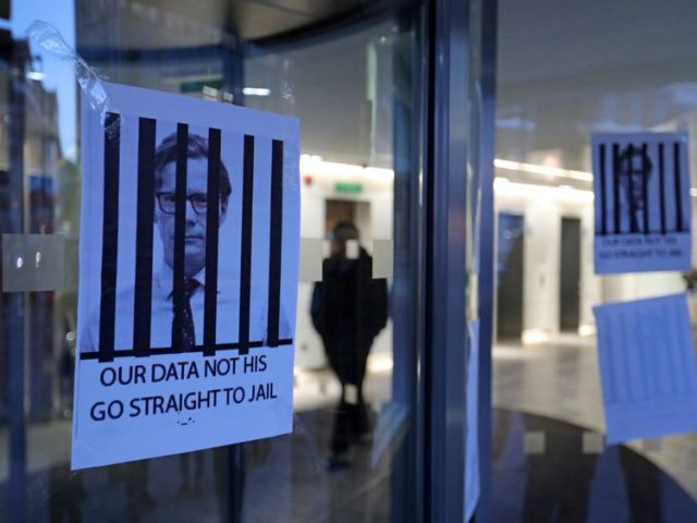 Posters depicting Cambridge Analytica's CEO Alexander Nix behind bars at the entrance of the company's London offices