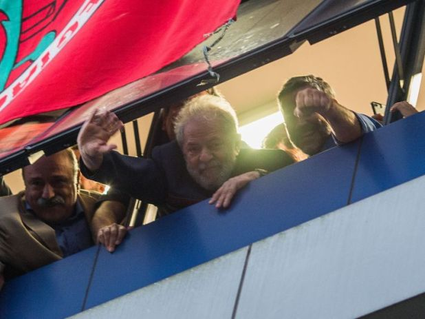 Lula da Silva waves to his supporters at the window of the Metalworkers' Union