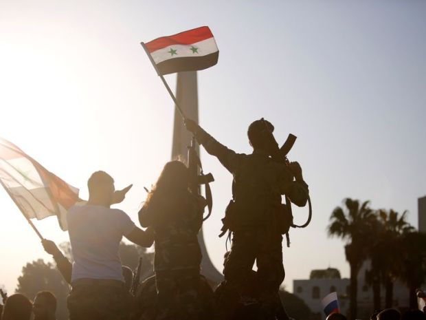 Syrians protest against US-led airstrikes on a street in Damascus