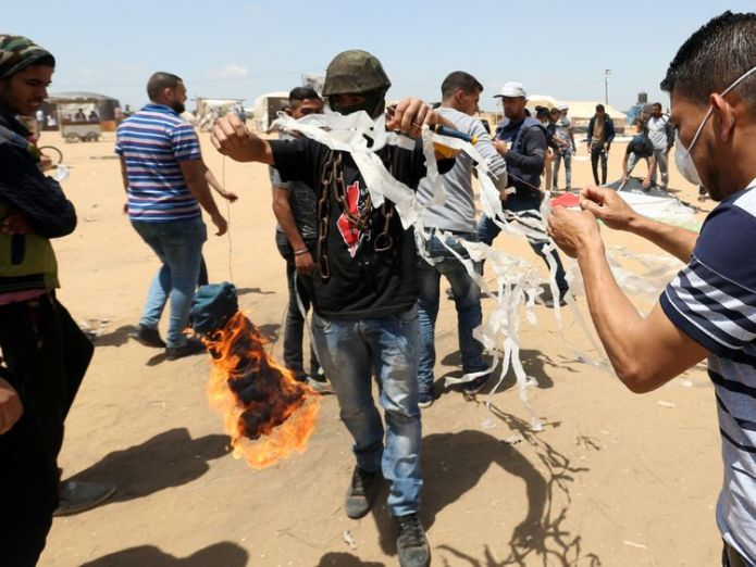 Palestinian demonstrators prepare to set a kite on fire to be thrown at the Israeli side  Palestinians shot dead as 'volatile' Gaza border protest intensifies Palestinians shot dead as 'volatile' Gaza border protest intensifies skynews gaza palestinian protests 4306741