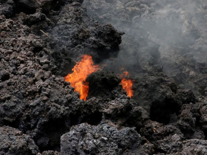 Flames are seen in a lava flow on Highway 137 southeast of Pahoa  Hawaii's Kilauea volcano spews toxic glass cloud as lava reaches ocean Hawaii's Kilauea volcano spews toxic glass cloud as lava reaches ocean skynews hawaii volcano kilauea 4316325