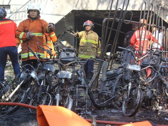 Firefighters at the Pantekosta Church survey the wreckage from the blast At least 11 dead in Indonesia church bombings at Sunday masses At least 11 dead in Indonesia church bombings at Sunday masses skynews indonedsia pantekosta church 4308443
