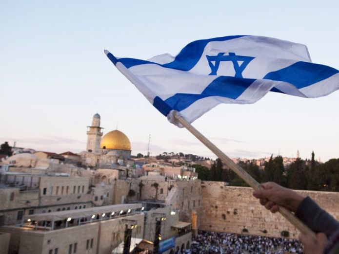 Israelis wave their national flags during a march next to the Western Wall on May 13, 2018 in Jerusalem, Israel Israel celebrates controversial US embassy move Israel celebrates controversial US embassy move skynews jerusalem embassy 4309739
