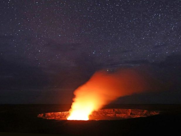 Stars shine above as a plume rises from the Halemaumau crater, illuminated by glow from the crater's lava lake, within the Kilauea volcano summit at the Hawaii Volcanoes National Park on May 9, 2018