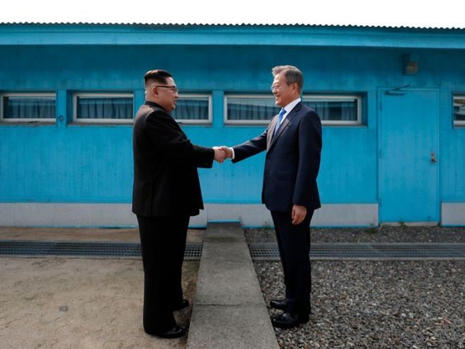 Kim Jong Un (L) and Moon Jae-in (R) shake hands over the military demarcation line
