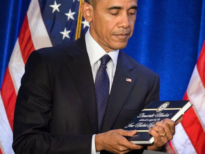 US President Barack Obama holds a copy of the Iran nuclear agreement presented to him by House Minority Leader Nancy Pelosi (D-CA) during the House Democratic Issues Conference January 28, 2016 in Baltimore, Maryland. / AFP / Brendan Smialowski (Photo credit should read BRENDAN SMIALOWSKI/AFP/Getty Images)