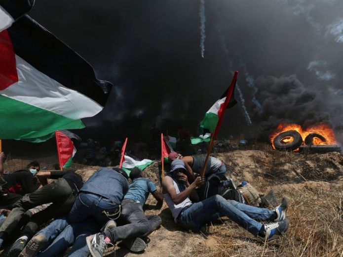 Palestinian demonstrators take cover from Israeli fire and tear gas during a protest against U.S. embassy move to Jerusalem and ahead of the 70th anniversary of Nakba, at the Israel-Gaza border in the southern Gaza Strip May 14, 2018 Theresa May calls for independent inquiry into 'tragic' Gaza deaths Theresa May calls for independent inquiry into 'tragic' Gaza deaths skynews palestinian gaza israel 4310529