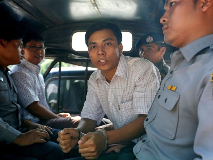 Detained Reuters journalist Kyaw Soe Oo (R) and Wa Lone (L) are transport in a police vehicle after a court hearing... myanmar military could be investigated over rohingya abuses Myanmar military could be investigated over Rohingya abuses skynews rohingya kyaw soe oo 4323909
